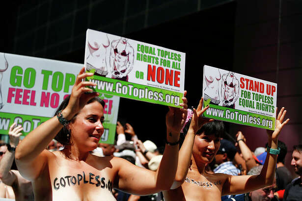 Activists hold posters as they take part in the GoTopless Pride Parade on August 28, 2016 in New York. Women around the US are going topless in celebration of GoTopless Day, focused on promoting gender equality and women's rights to bare their breasts in public.