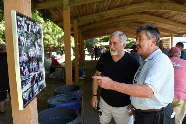 Cos Cob residents Milo Fuscaldo, left, and Jim Capparelle look at photos of club members from past picnics at the Cos Cob Mianus Dugout Old Timers picnic at Greenwich Point Park in Old Greenwich, Conn. Sunday, Aug. 28, 2016. Dozens of folks enjoyed the 32st annual picnic, featuring burgers, hot dogs, ribs and more from Jerry's Post Road Market in Rye, N.Y.  Partygoers got the chance to catch up with one another and remininisce on old memories while eating and playing games like bocce, cornhole and cards.  The Dugout Old Timers club was formed in 1984 in the basement of Bruno's Tavern at the location of what is now Louie's in Cos Cob.