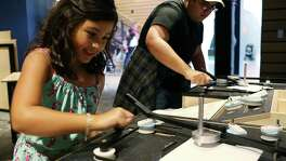 Mattie Herrera 8, draws symmetrical patterns with her uncle, Richard Garcia, 17, at the Mathletics exhibit at the DoSeum, Sunday, August 28, 2016. The exhibit lets the public explore fundamental math concepts.