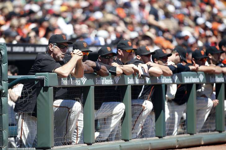 San Francisco Giants manager Bruce Bochy, left, watches the game  against the Atlanta Braves from the dugout during the first inning at AT&T Park on Sunday, August 28, 2016, in San Francisco, California.