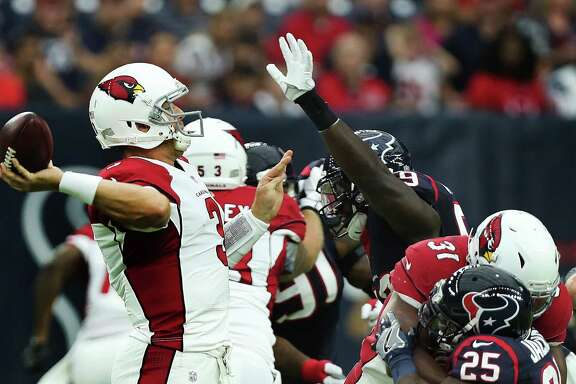 Arizona Cardinals quarterback Carson Palmer (3) passes under pressure of the Texans defense during the first quarter of an NFL pre-season football game at NRG Stadium on Sunday, Aug. 28, 2016, in Houston.