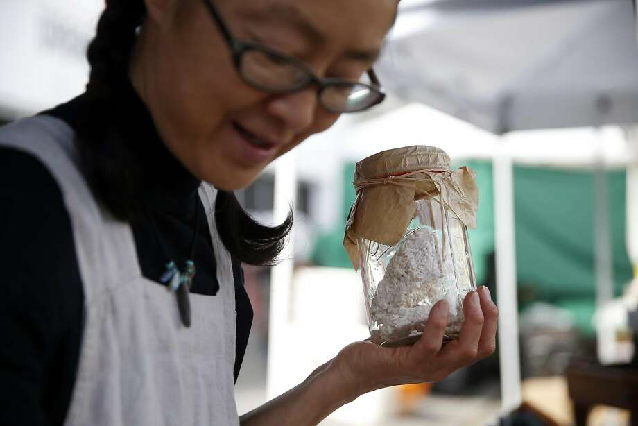 Mariko Grady shows a customer fresh rice koji at the Aedan Fermented Foods booth at the Divisadero Farmers' Market in San Francisco. Photo: Scott Strazzante, The Chronicle
