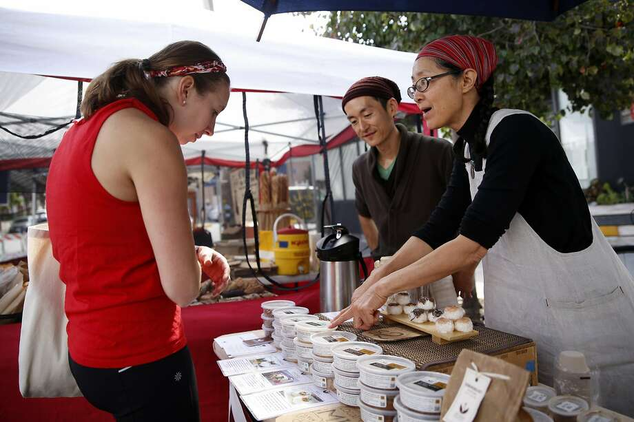 Sattee Fujimoto (left) and Mariko Grady describe their products to customer Rebecca Gilbert at the Aedan Fermented Foods booth at the Divisadero Farmers' Market in San Francisco. Photo: Scott Strazzante, The Chronicle