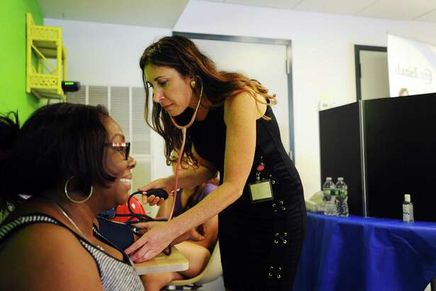 Ricki Goldstein, of DanielCare, takes a patrons blood pressure free of charge during the New Neighborhood's multi-agency heath fair at Martin Luther King Jr. Apartments, on the west side of Stamford, Conn., on Thursday, August 25, 2016.