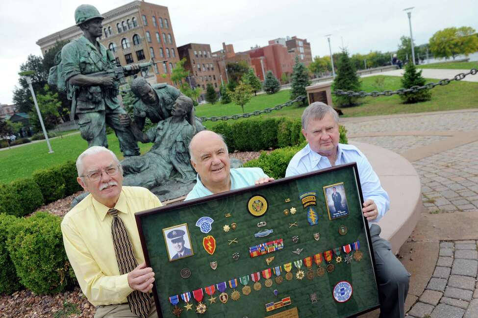 Dave Barnum, left, and John Mullen, right, both of the Rensselaer County Vietnam Veterans Memorial Committee, join Jim Quamo of Spencerport, center, on Tuesday, Sept. 29, 2015, at Riverfront Park in Troy, N.Y. Barnum and Mullen are working a campaign to have Quamo's brother, George Quamo, awarded a Medal of Honor. George Quamo, who's shadow box they hold, was a Green Beret soldier from Averill Park and led a heroic rescue mission in Vietnam. (Cindy Schultz / Times Union)