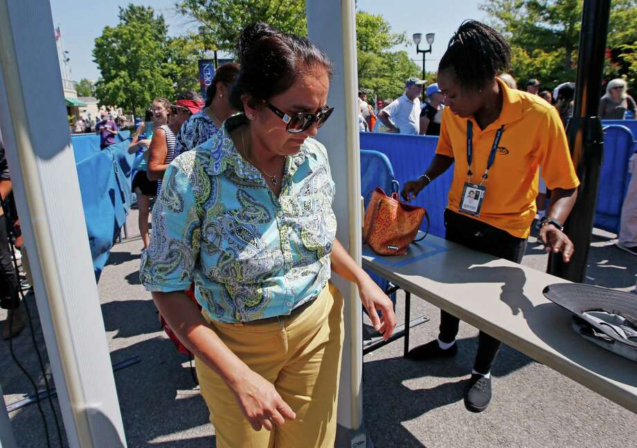 In this Wednesday, Aug. 24, 2016 photo, a woman passes through a metal detector for security screening while entering the grounds of the Billie Jean King National Tennis Center in New York during qualifying rounds for the U.S. Open Tennis Tournament. With more than 700,000 fans expected, the U.S. Open tennis tournament poses unique security challenges for officials charged with making the grounds safe. (AP Photo/Kathy Willens) ORG XMIT: NYKW502 Photo: Kathy Willens / Copyright 2016 The Associated Press. All rights reserved. This m