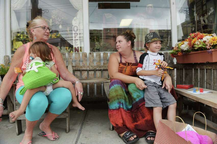 Diane McDermott, left, owner of Little Posy Place, sits outside her Main Street store with her daughter, Dawn Failing, and Failing's children, Italia, 2, and Avalon, 5, on Thursday, Aug. 25, 2016, in Schoharie, N.Y. McDermott opened the shop after the flooding to help the town rebuild its businesses. Failing and her husband lost their home in the flooding. (Paul Buckowski / Times Union)