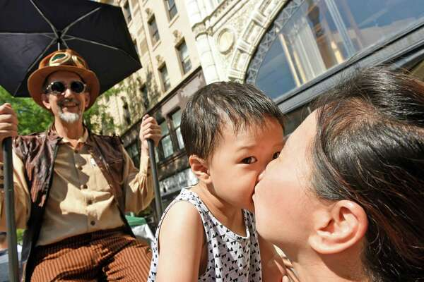 "On-year-old Preston Choi gets a kiss from his grandmother Young Cho of Latham during the third annual ""The Enchanted City"" urban street faire, a spectacle of steampunk fashion, fantasy and fabrications transformed the historic blocks of downtown Troy on Saturday Aug. 27, 2016.  (Michael P. Farrell/Times Union)"