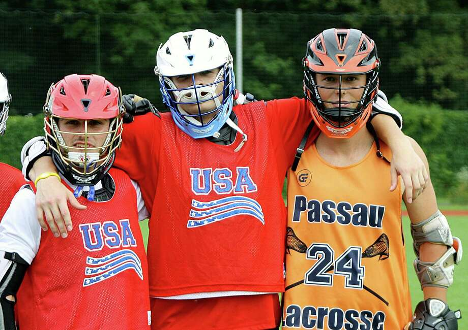 Nolan Quinn, center, stands next to a Team USA teammate and an opponent from Germany while making an appearance during an ACIS Educational Tour in Europe to promote the game of lacrosse. Photo: Contributed Photo / Norwalk Hour