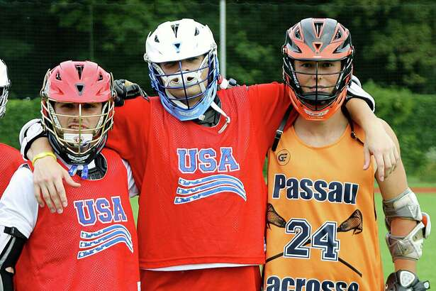Nolan Quinn, center, stands next to a Team USA teammate and an opponent from Germany while making an appearance during an ACIS Educational Tour in Europe to promote the game of lacrosse.