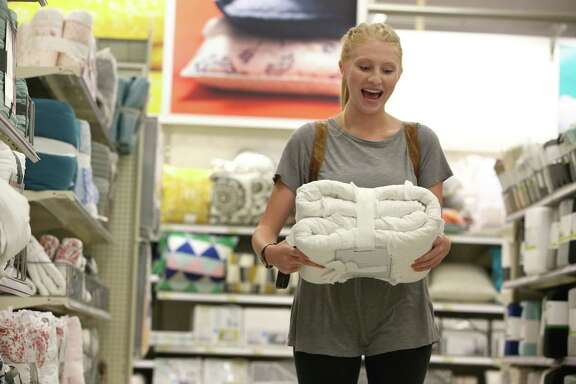 College senior Alison Catalano is all smiles after finding the bedspread she'd been looking for at a Target store in Lake Zurich, Ill. Consumer spending posted its fourth straight monthly increase in July, a sign that the economy is posed for a rebound.