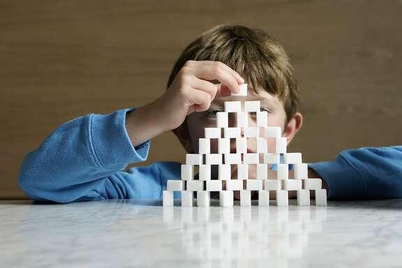 Boy (6-8) building sugar cube tower