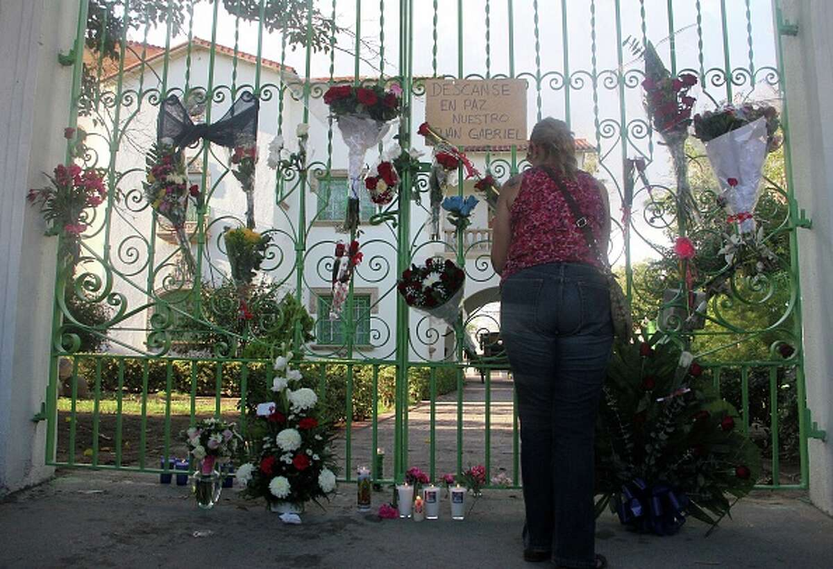 """A woman puts flowers in front of the house of Mexican singer Juan Gabriel in Ciudad Juarez, Mexico on August 28, 2016. Mexican singer, composer and producer Alberto Aguilera Valadez, better known as """"Juan Gabriel"""", died on August 28, 2016 in Santa Monica, California, U.S.A. from a heart attack / AFP / HERIKA MARTINEZ (Photo credit should read HERIKA MARTINEZ/AFP/Getty Images)"""
