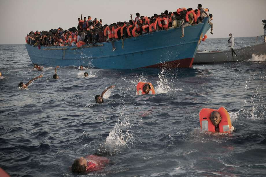Migrants, most of them from Eritrea, leap into the water from a crowded boat during a rescue operation in the Mediterranean Sea about 13 miles north of Sabratha, Libya. Photo: Emilio Morenatti, Associated Press