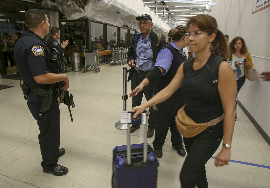 A police officer stands guard at Los Angeles International Airport. False reports of an active gunman Sunday caused panicked evacuations. Photo: Ringo H.W. Chiu, Associated Press