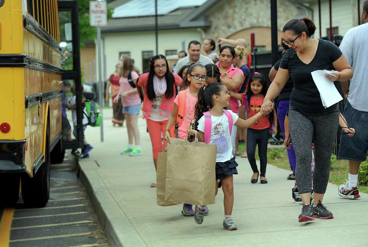 Emilia Ortega, 4, holds her mother Luisana's hand, as she arrives for the first day of school at Ellsworth Avenue Elementary in Danbury, Monday, August 29, 2016. Behind her is sister Camila, 8.