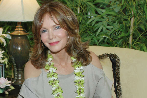 Actress Jaclyn Smith sits on one of her signature sofas at the Navy Exchange in Pearl Harbor, Hawaii, Saturday, June 17, 2006.  Smith made an appearance in Pearl Harbor to introduce her home furnishings line, which includes upholstered and wood furniture, bedding and fabric.   (AP Photo/Ronen Zilberman)