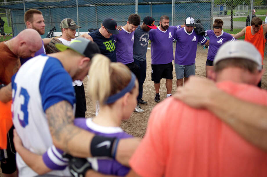 BRITTNEY LOHMILLER | blohmiller@mdn.net M Drycleaners and Orange Crush softball teams gather in prayer after their game Saturday morning at New Red Coats Field in Midland. 'Want to stay clean, want to stay sober?' tournament organizer Charlie London said. 'You got to get out and do something positive. That's what this is.' Eight teams from around the state comprised of people in recovery from addictions started playing in a tournament before heavy rains forced the tournament to be postponed. / Midland Daily News
