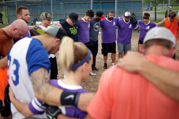 BRITTNEY LOHMILLER | blohmiller@mdn.net M Drycleaners and Orange Crush softball teams gather in prayer after their game Saturday morning at New Red Coats Field in Midland. 'Want to stay clean, want to stay sober?' tournament organizer Charlie London said. 'You got to get out and do something positive. That's what this is.' Eight teams from around the state comprised of people in recovery from addictions started playing in a tournament before heavy rains forced the tournament to be postponed.