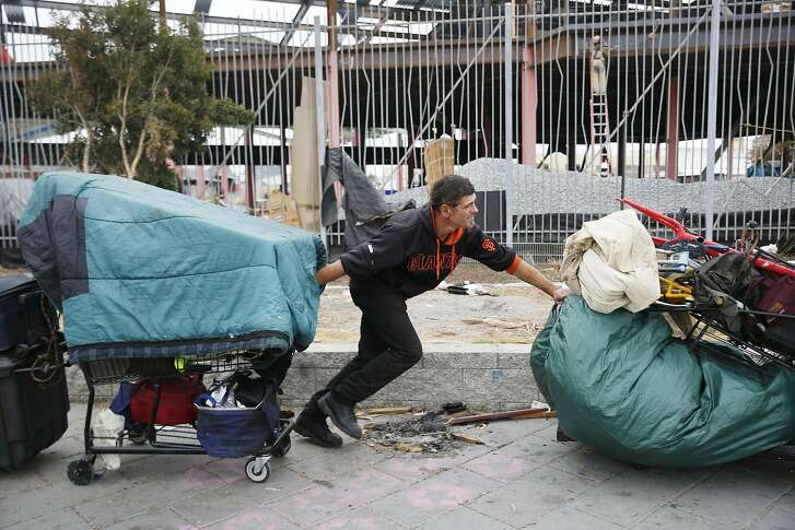 Joaquin Tellez, who says he has been dealing with homelessness off and on since 2000, pushes one cart while pulling another filled with his belongings at the Islais Creek homeless encampment as it is cleared on Monday, August 29,  2016 in San Francisco, California.