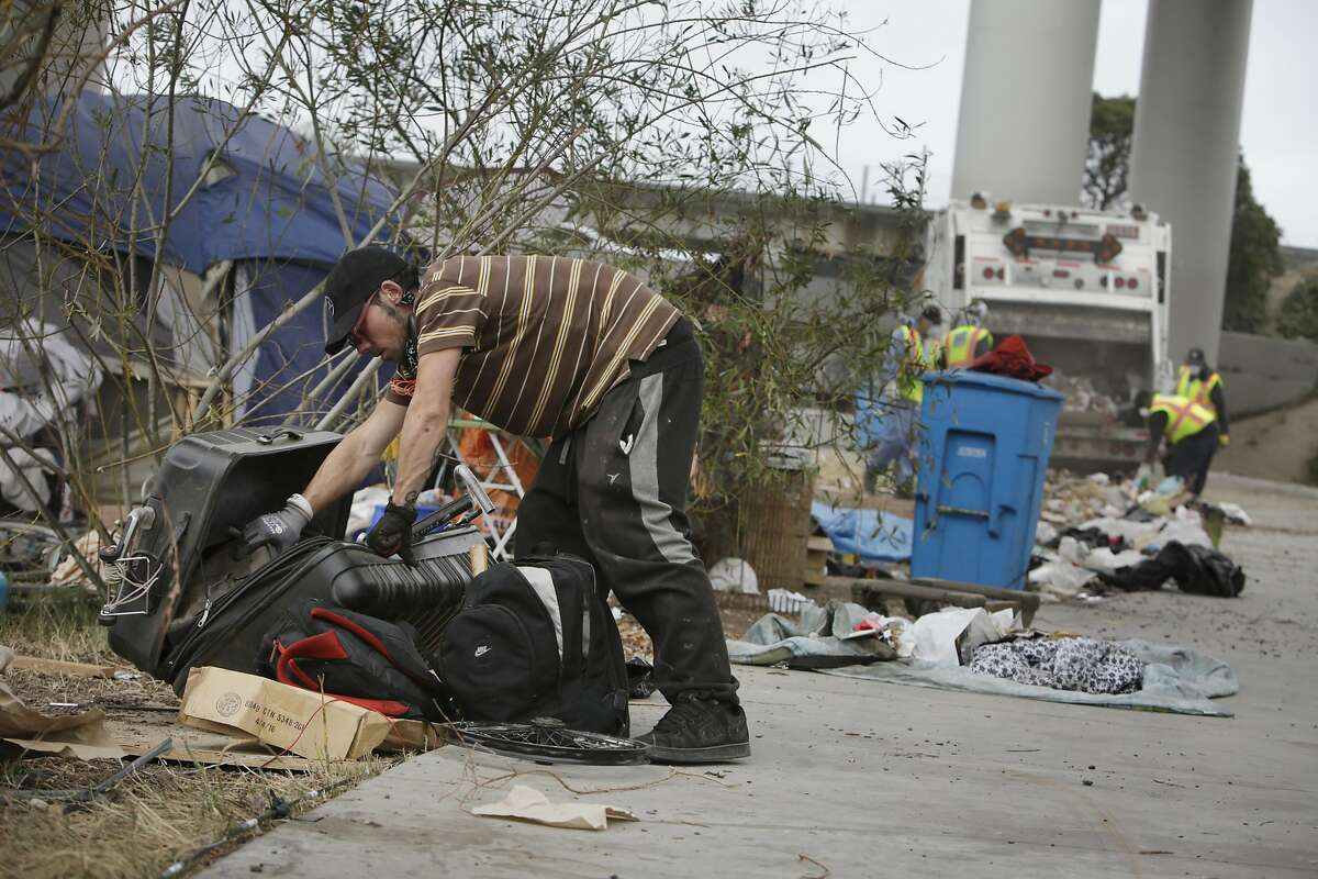 Steven Payton, who says he has been dealing with homelessness off and on for 9 months, looks through a suitcase at the Islais Creek homeless encampment as he helps a friend move on the day the encampment is cleared on Monday, August 29, 2016 in San Francisco, California.