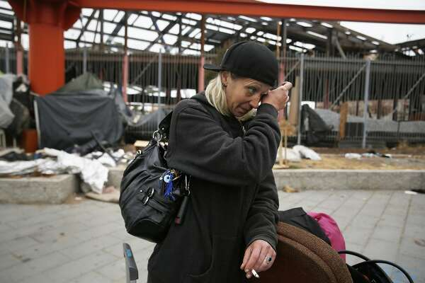 """""""Vengence"""" who says she has been dealing with homelessness for 13 years, wipes a tear from her eye while talking about her situation, as she moves some of her belongings at the Islais Creek homeless encampment as she prepares to move to the Navigation Center on Monday, August 29,  2016 in San Francisco, California."""