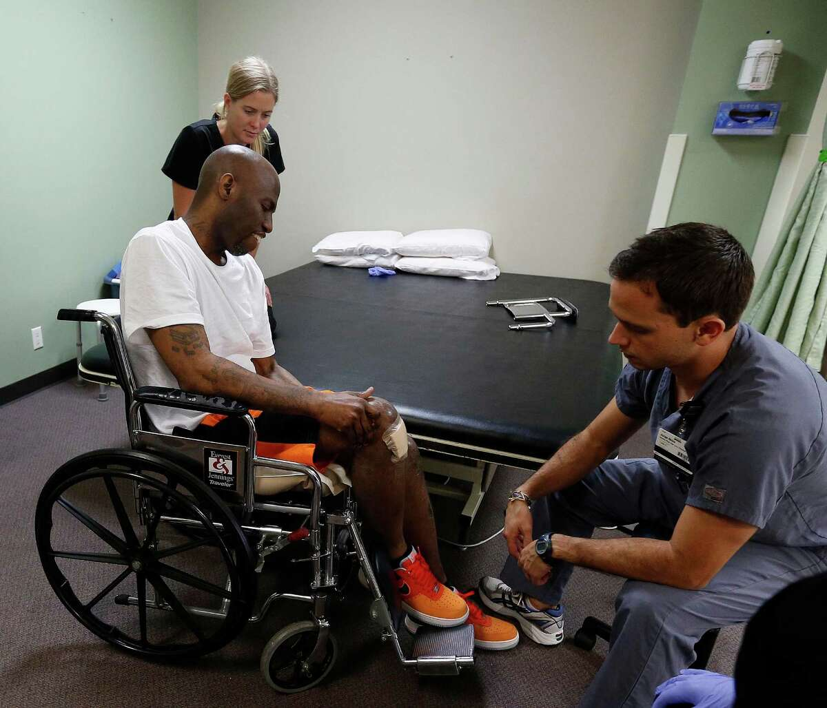 Quincy Davis works with physical therapist, Jorge Neira, and OTR student, Lindsay Eckert at the Quentin Mease Community Hospital, Friday, Aug. 12, 2016, in Houston. Davis and his family say that he was denied proper medical treatment during his two years in the Waller County Jail, where he was awaiting trial on charges for drugs and for assaulting police. After a month in two hospitals, he is now at this rehab hospital.