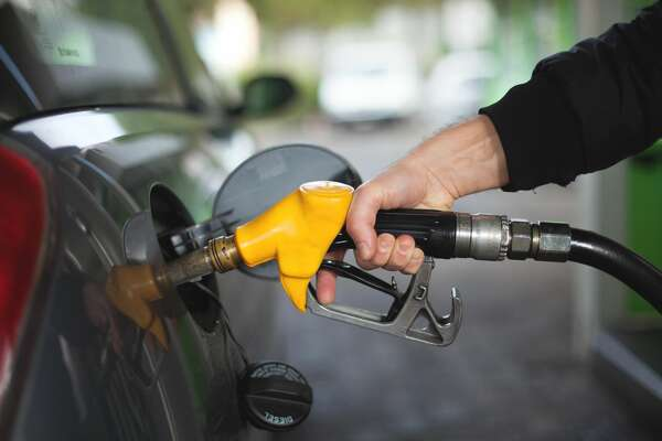 Hand of man fueling up a vehicle with a yellow gas pump.