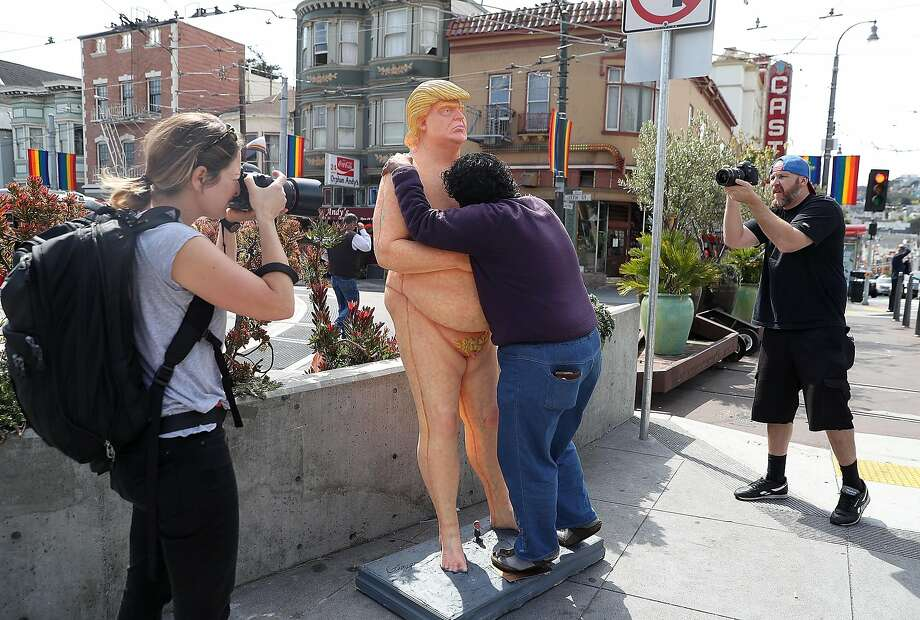 Photographers take pictures of a passerby as she hugs a statue depicting a nude Donald Trump on Aug. 18. Photo: Justin Sullivan, Getty Images