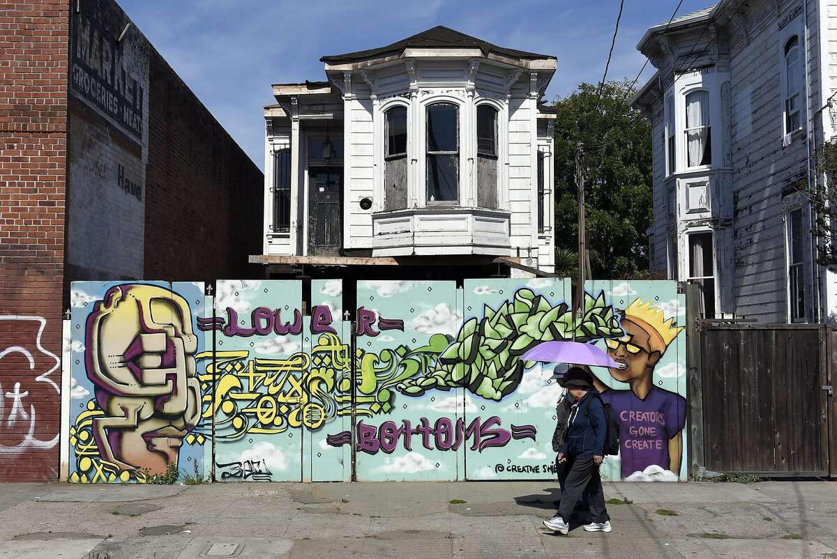 People walk past the site of one of Bruce Loughridge's restoration projects on Peralta Street in West Oakland, CA Monday, August 29, 2016.