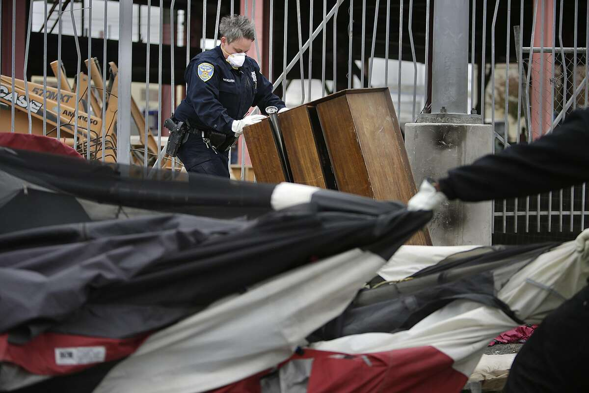 Officer Yvonne Moilanen works to remove a tent at the Islais Creek homeless encampment on Monday, August 29, 2016 in San Francisco, California.