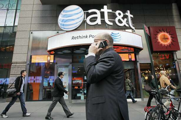 In this Oct. 18, 2011 photo, a man using a cell phone passes an AT&T store, in New York.   AT&T Inc. on Thursday, Oct. 20, 2011,  reported a decline in the number of iPhones activated in its latest quarter, as buyers waited for the new model. ((AP Photo/Mark Lennihan)