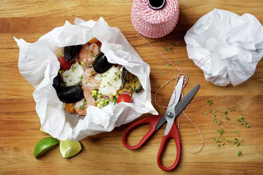 Prepared in parchment paper, a meal of corn, tomato, herbs topped with scallops, mussels and shrimp steams effortlessly. Photo: Deb Lindsey / For The Washington Post