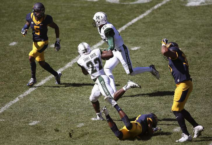 Hawaii Rainbow Warriors' Diocemy Saint Juste, center, breaks a tackle by California Golden Bears' Khari Vanderbilt second right, on his way to scoring a touchdown during the opening game of the U.S. college football season at Sydney's Olympic stadium in Sydney, Saturday, Aug. 27, 2016. The last American football of any kind played in Sydney was an NFL preseason game at the Olympic stadium that attracted 73,000 spectators in 1999. (AP Photo/Rick Rycroft)