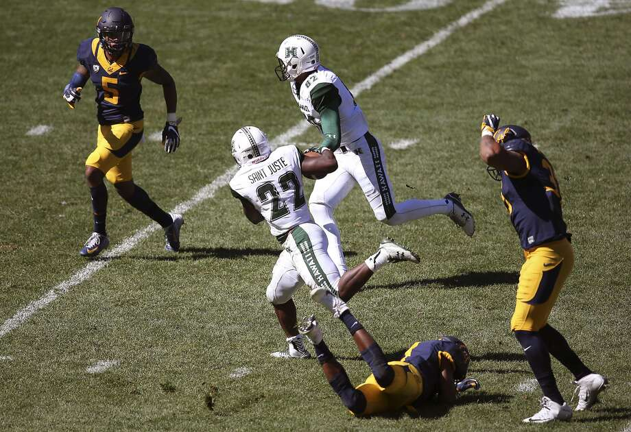 Hawaii Rainbow Warriors' Diocemy Saint Juste, center, breaks a tackle by California Golden Bears' Khari Vanderbilt second right, on his way to scoring a touchdown during the opening game of the U.S. college football season at Sydney's Olympic stadium in Sydney, Saturday, Aug. 27, 2016. The last American football of any kind played in Sydney was an NFL preseason game at the Olympic stadium that attracted 73,000 spectators in 1999. (AP Photo/Rick Rycroft) Photo: Rick Rycroft, Associated Press
