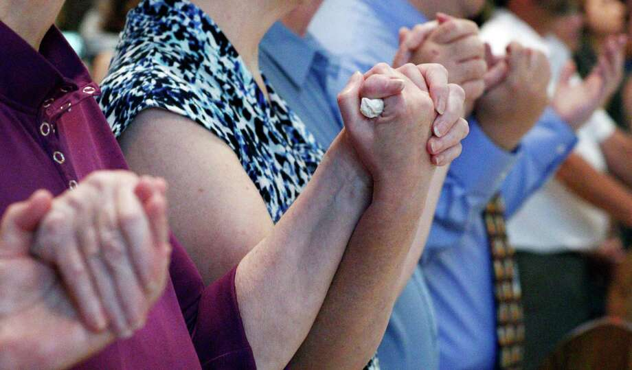Family members of Sister Paula Merrill, hold hands during a memorial Mass for Merrill and Sister Margaret Held, Aug. 29,  Photo: Rogelio V. Solis, STF / Copyright 2016 The Associated Press. All rights reserved. This material may not be published, broadcast, rewritten or redistribu