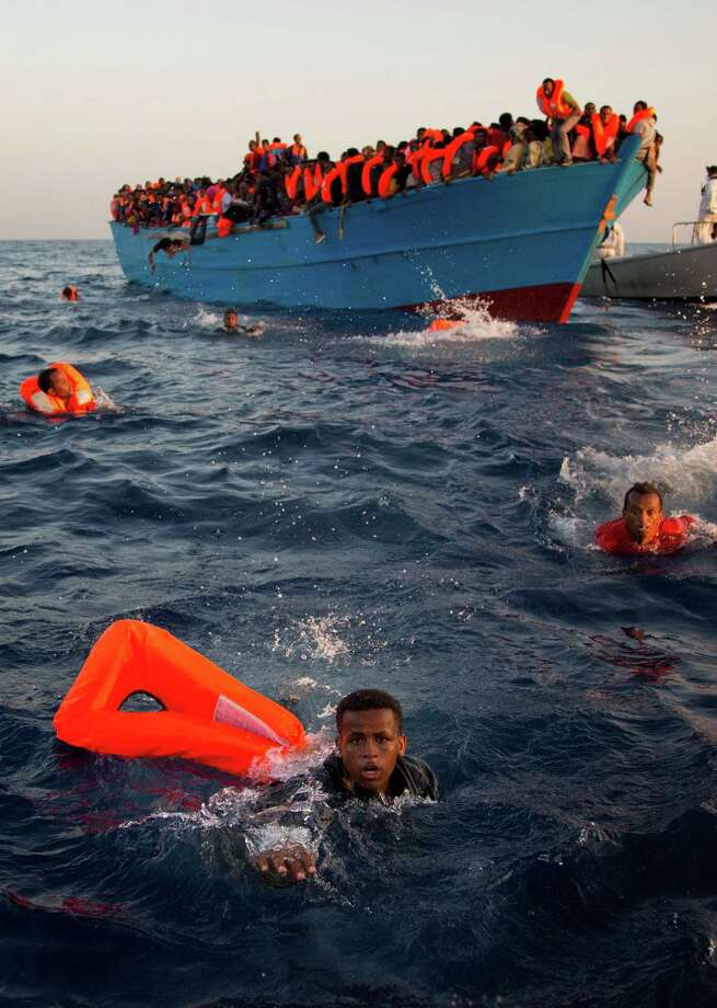 Migrants, most from Eritrea, jump into the Mediterranean Sea from a crowded wooden boat to await rescue Monday by bigger ships near Sabratha, Libya. Tens of thousands of Africans take the route as a gateway to a better life in Europe. Photo: Emilio Morenatti, STF / Emilio Morenatti