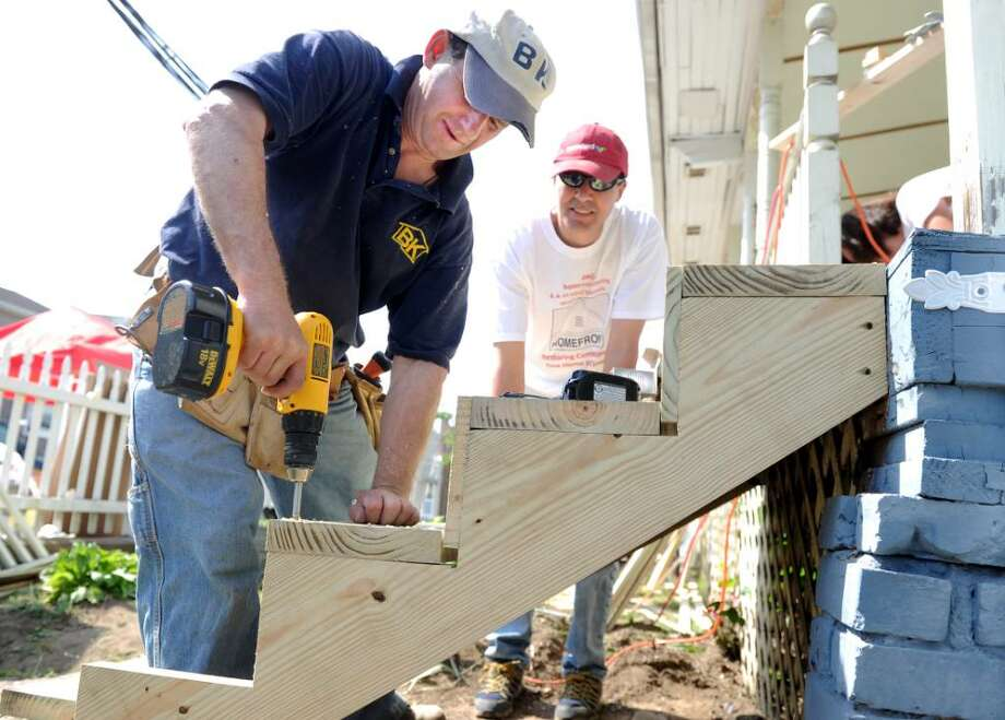 Bogden Karwowski, left, and John Holmes, both of Weston, work on building new front steps for a home on Butler Avenue in Bridgeport Saturday May 1, 2010 during the 23rd annual HomeFront Day where volunteers spend a day fixing up local properties. Photo: Autumn Driscoll / Connecticut Post