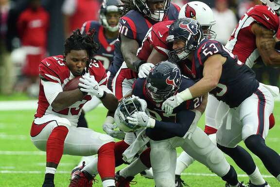 The Cardinals' Chris Johnson, left, runs into trouble against a Texans defense that will be even more formidable with the pending return of J.J. Watt.