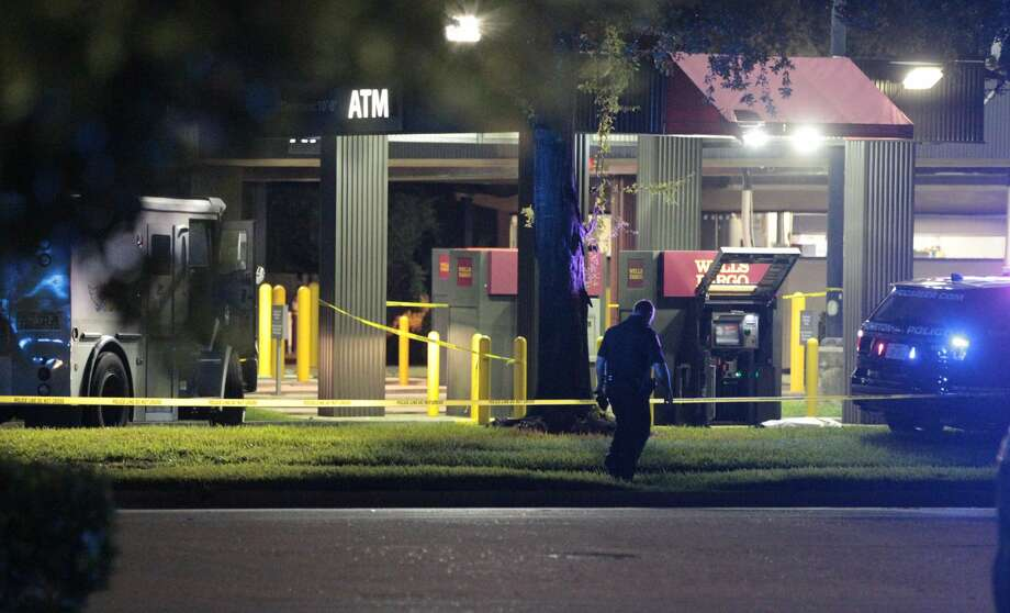 A Houston Police Officer at the scene of a robbery of an ATM which was being serviced at the Wells Fargo bank at Highway 290 and Hollister on August 29, 2016. Photo: James Nielsen / Houston Chronicle