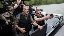 In this FILE PHOTO, Lieutenant Governor Dan Patrick, right, accompanied by the director of the Texas Department of Public Safety Steven McCraw, left, takes photos during a ride on a super shallow waters boat acquired by DPS with Texas state funds. Patrick reviewed border security improvements as well as speaking with the different law enforcement agencies working on the border. Tuesday, March 8, 2016. ( Marie D. De Jesus / Houston Chronicle )