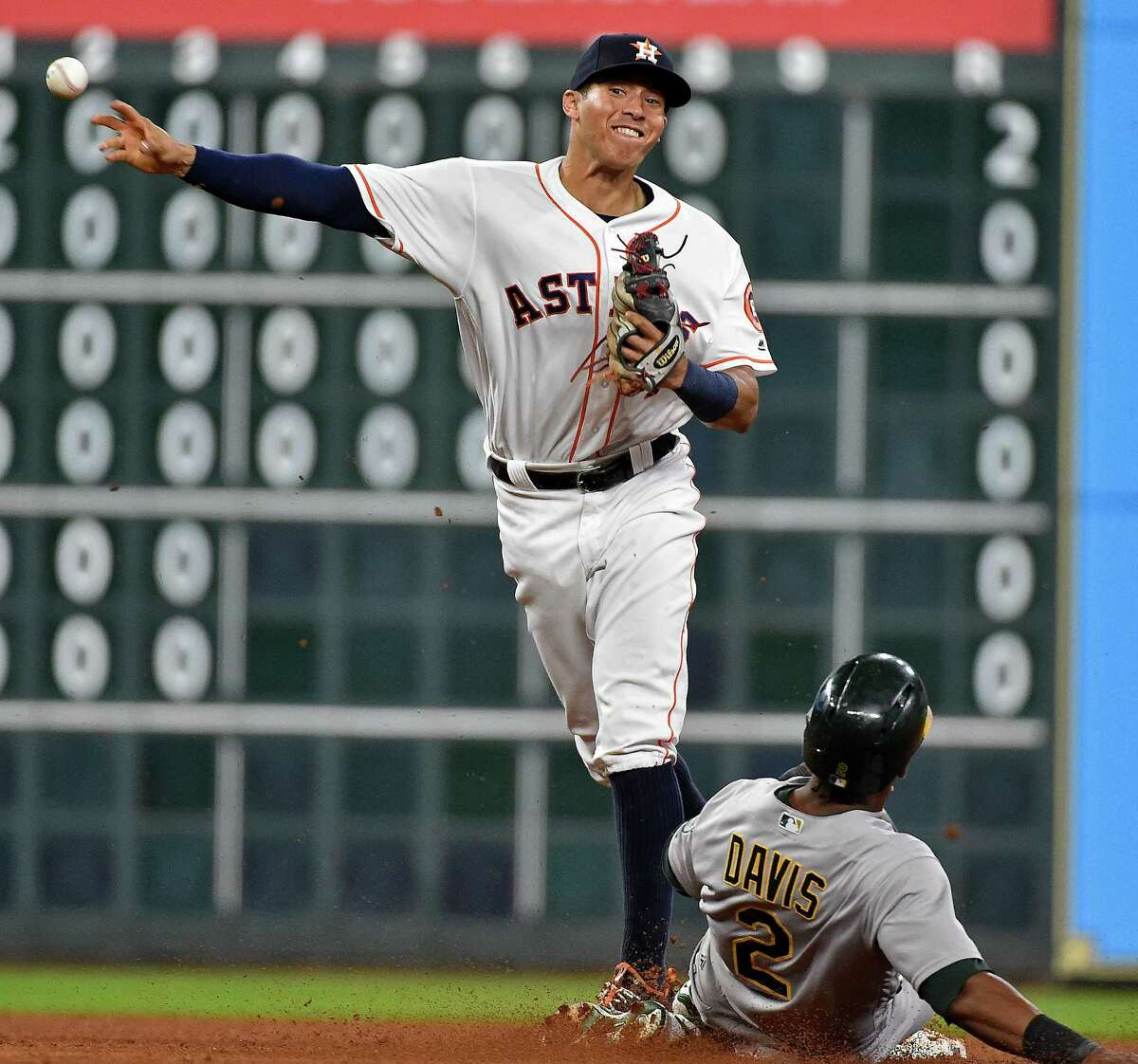 Houston Astros shortstop Carlos Correa, left, turns a double play over Oakland Athletics' Khris Davis to end the sixth inning of a baseball game, Monday, Aug. 29, 2016, in Houston. (AP Photo/Eric Christian Smith)