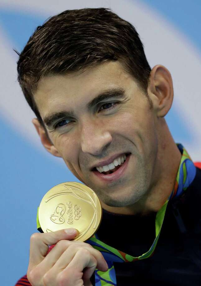 FILE - In this Aug. 14, 2016 file photo, United States' Michael Phelps displays his gold medal for the men's 4 x 100-meter medley relay final during the swimming competitions at the 2016 Summer Olympics in Rio de Janeiro, Brazil. The most decorated Olympian of all time, swimmer Phelps, offered a name to go with his famous Phelps face Sunday, Aug. 28, and it's one word: Future. (AP Photo/Michael Sohn, File) Photo: Michael Sohn, STF / Copyright 2016 The Associated Press. All rights reserved. This material may not be published, broadcast, rewritten or redistribu