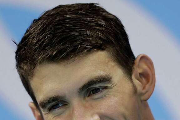 FILE - In this Aug. 14, 2016 file photo, United States' Michael Phelps displays his gold medal for the men's 4 x 100-meter medley relay final during the swimming competitions at the 2016 Summer Olympics in Rio de Janeiro, Brazil. The most decorated Olympian of all time, swimmer Phelps, offered a name to go with his famous Phelps face Sunday, Aug. 28, and it's one word: Future. (AP Photo/Michael Sohn, File)
