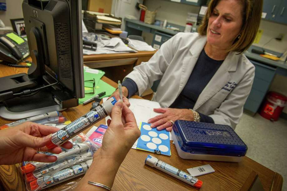 Diane Voelker, a school nurse, looks over EpiPens in Ashburn, Va., in 2012. In another move to quell outrage over its price increases, the maker of the EpiPen will introduce a generic version of the product. Photo: KAREN KASMAUSKI, STR / NYTNS