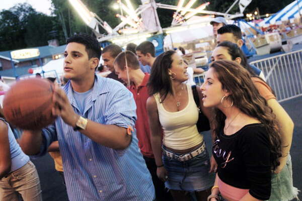 Stamford_083104_ Jamie Ely, 13, right, watches Ahmed Elkady, 14, shoot for a prize, while Brooke Girardi, 15, center, talks to a friend at the St. Leo's Fair at St. Leo's Parish on Roxbury Road. The fair runs through this Saturday. Chris Preovolos/Staff Photo