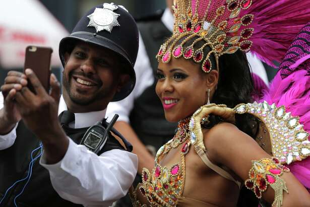 A performer poses for a selfie with a policeman on the second day of the Notting Hill Carnival in west London on August 29, 2016.  Nearly one million people are expected by the organizers Sunday and Monday in the streets of west London's Notting Hill to celebrate Caribbean culture at a carnival considered the largest street demonstration in Europe.
