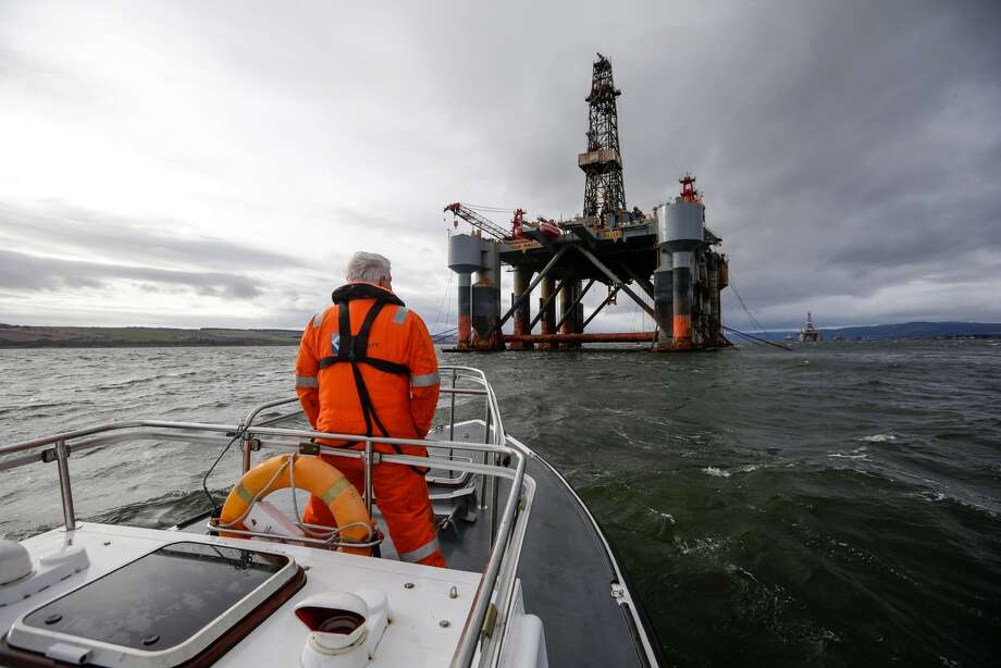 An employee stands on the deck of a pilot boat in view of the Ocean Princess oil platform, operated by Diamond Offshore Drilling Inc., in the Port of Cromarty Firth in Cromarty, Scotland, on Feb. 16, 2016. Photo: Matthew Lloyd, Bloomberg