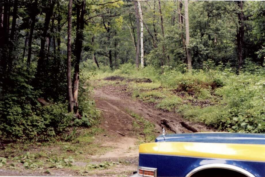 """A state police cruiser parked at the scene where 15-year-old Robert """"Bobby' Gutkaiss' decomposing body was found. State Police said they continue to investigate his 1983 homicide. (State Police) Photo: State Police"""