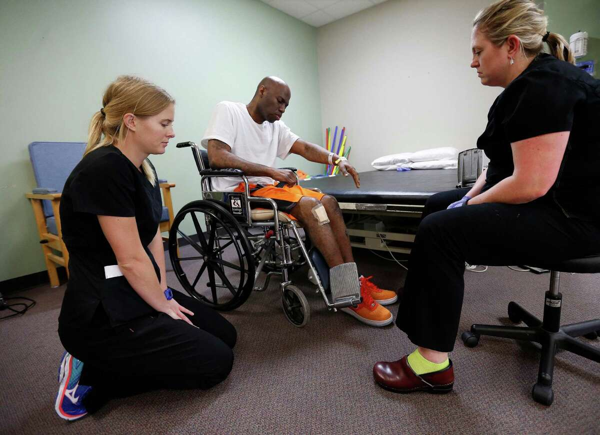 Quincy Davis works with OTR student, Lindsay Eckert, left, and occupational therapist Amy Herbster, right, at the Quentin Mease Community Hospital, Friday, Aug. 12, 2016, in Houston. Davis and his family say that he was denied proper medical treatment during his two years in the Waller County Jail, where he was awaiting trial on charges for drugs and for assaulting police. After a month in two hospitals, he is now at this rehab hospital.